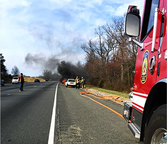 Highway with smoking car and fire engine on side of road